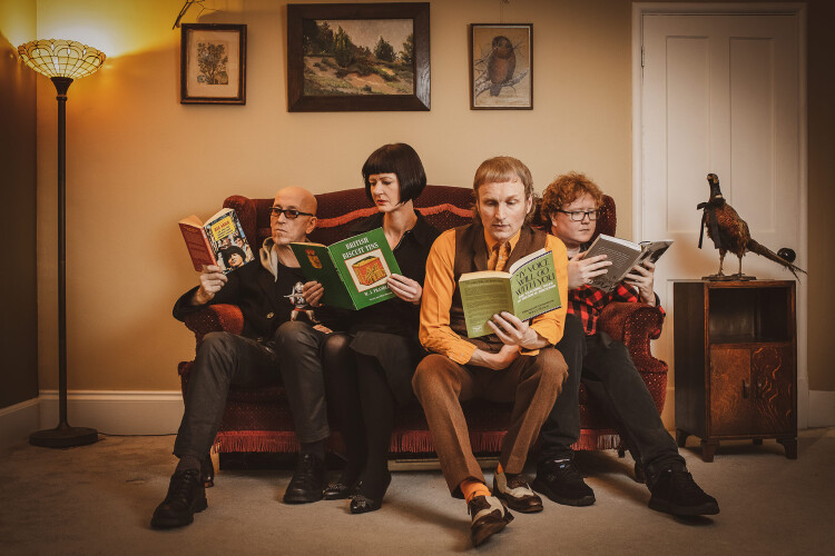 Micko & The Mellotronics sat on a sofa reading interesting books