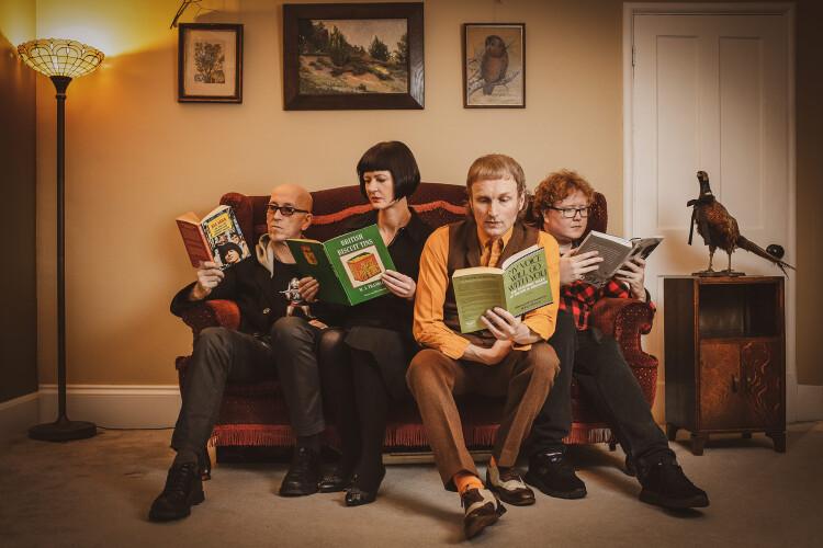 Micko & The Mellotronics sat on a sofa reading interesting books